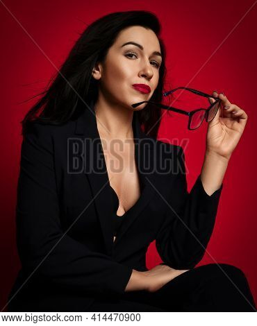 Portrait Sexy Mature Brunette Woman In Official Suit With Deep Neckline Sitting Taking Off Her Glass