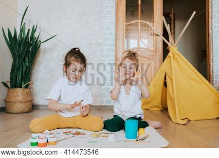 Two Children In Light Clothes Sit On The Floor On Their Knees And Enthusiastically Draw With Bright