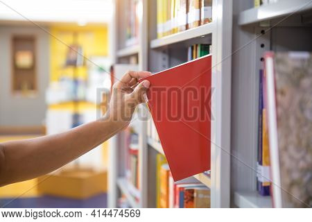 Close Up Hand Choosing And Picking A Book From Bookshelf In The Library. Concepts Of Reading Textboo