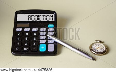 The Word Addiction Is Written On The Calculator's Display, Next To A Pen And A Clock. Health And Dru