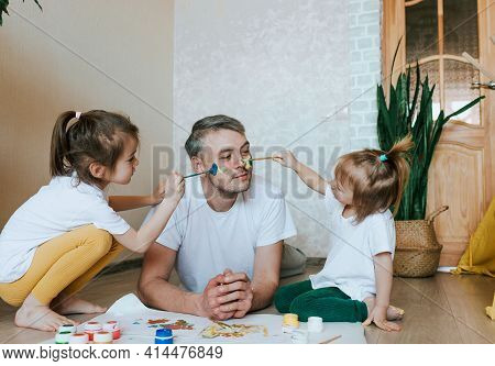Two Little Girls Paint On Dad's Face With Paint. Happy Father
