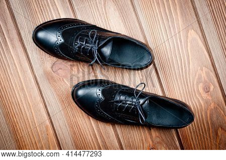 Black Imitation Leather Shoes Laced With Wide Laces. Close-up Shot.