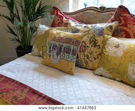 Richly-patterned cushions on luxurious bed