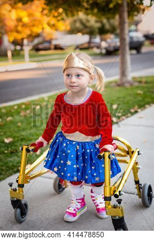 Disability photo of a cute little disabled girl walking with a special walker outdoors on the sidewalk