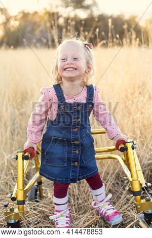 Disability photo of a cute young disabled girl walking with a special walker outdoors. Vertical portrait of a young girl who loves being outside. Her efforts to walk and live a normal life are heroic.
