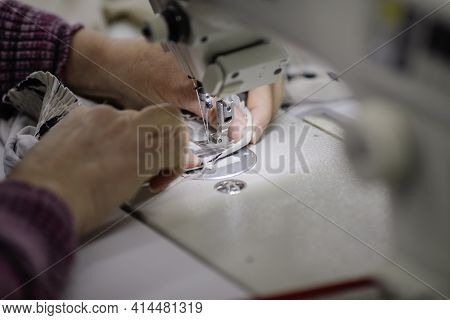 Shallow Depth Of Field (selective Focus) Image With The Hands Of A Senior Woman Working At An Electr