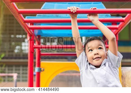 Kid Exercise For Health And Sport Concept. Happy Asian Student Child Boy Playing And Hanging From A