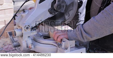 Sawing Off Wooden Blocks On A Woodworking End Machine, A Carpenter At Work At A Bevelling Machine, A