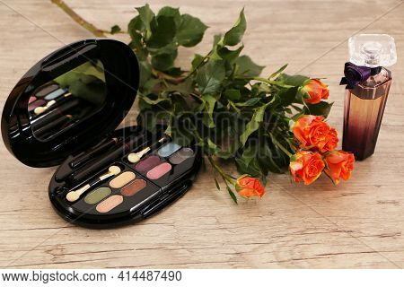 A Set Of Perfumes On A Wooden Table, Decorated With A Bouquet Of Roses. The Background Is White. Bea