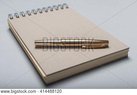 Notebookor Notepad And Golden Pen On Desk