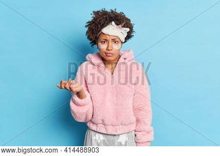 Confused Dark Skinned Young Woman With Curly Hair Wears Sleepmask Raises Palm Hesitant Applies Colla