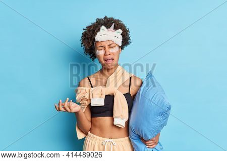 Horizontal Shot Of Dejected Afro American Woman Cries From Despair Dressed In Nightwear Holds Pillow