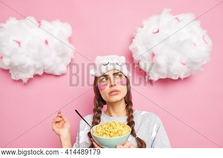 Pleasant Looking Thoughtful European Woman Concentrated Above Wears Sleepmask And Pajama Holds Bowl