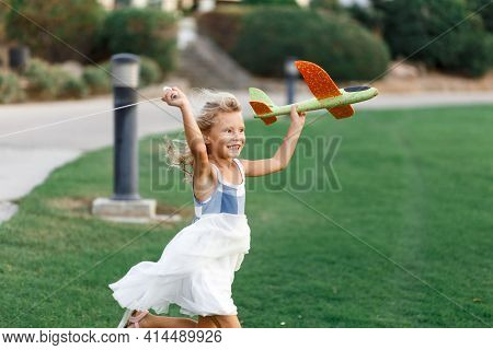 Little Girl, Launches A Toy Plane, Into The Air Against, The Background Of Green Grass. Child Launch