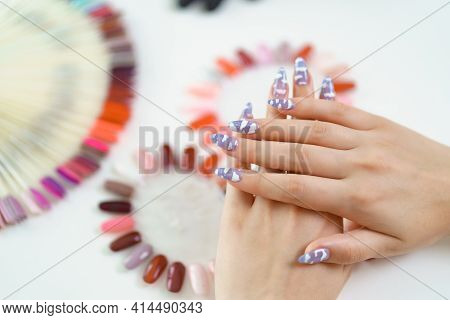 Well-groomed Hands And Nail Color Samples. Female Hands With Pastel Manicure And Nail Color Palette.