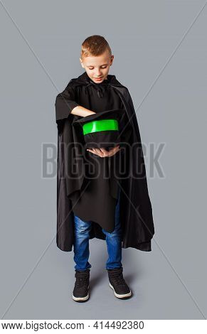 Little Magician Does Tricks. Child Magician Holding A Top Hat With Suprise.