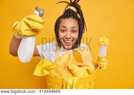 Positive Female Housekeeper Wears Protective Rubber Gloves Does Home Cleaning Routine Holds Brush An