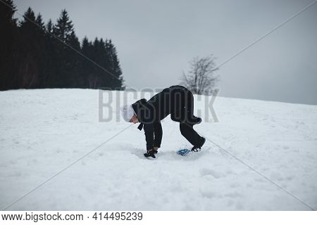 Athlete Falls From A Plastic Snowboard And Falls Hard On The Snow And Sprawls. The Boy's Board Got S