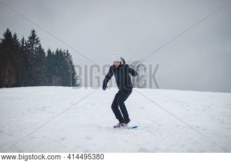 Youth Falls From A Plastic Snowboard And Falls Hard On The Snow And Sprawls. The Boy's Board Got Stu