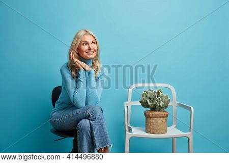 Indoor Shot Of Wrinkled Pleased Dreamy Grandmother Poses On Comfortable Chair Moves In New Flat Sits
