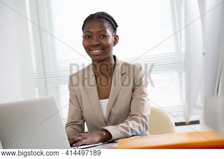 Portrait of pretty african american business woman looking at camera at workplace in an office