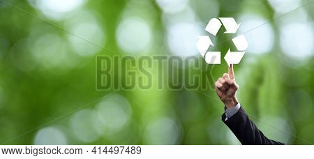 Businessman In Suit Over Natural Green Background Holds An Recycling Icon, Sign In His Hands. Ecolog