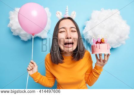 Bad Holiday Concept. Sad Stressful Asian Woman Cries From Despair Holds Inflated Balloon And Tasty D