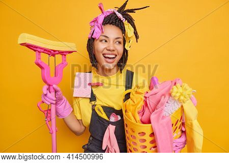 Happy Young African American Housewoman Holds Mop And Basin Of Laundry Looks Gladfully Aside Glad To