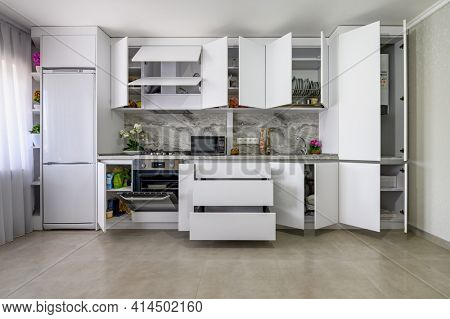 Well designed white modern kitchen interior, drawers are pulled out, doors opened, straight front view