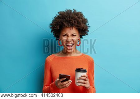 Angry Irritated African American Woman Uses Mobile Phone Screams Loudly Smirks Face Drinks Coffee To