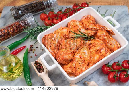 Rmarinated Chicken Wings With Different Vegetables On A Marble Kitchen Board In A Bowl For Baking In