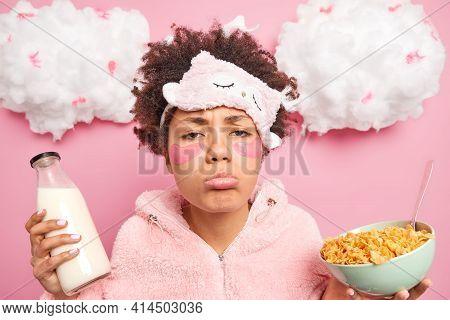 Sleepy Sulking Afro American Woman With Sad Expression Wears Nightwear Eats Healthy Food Applies Col