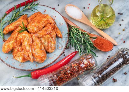Marinated Chicken Wings With Different Vegetables On A Marble Kitchen Board.marinated Chicken Wings