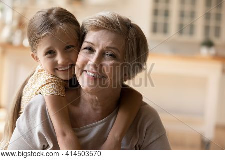 Portrait Of Happy Grandmother And Granddaughter Hugging
