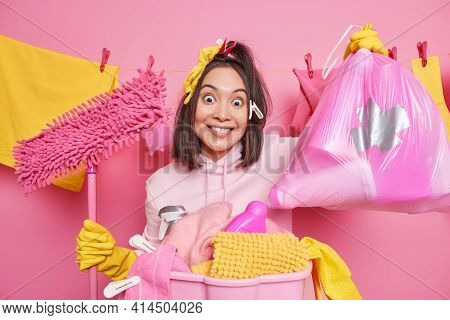 Spring Cleaning Concept. Positive Asian Housewife Holds Mop Bag Of Cleaning Detergents Does Laundry