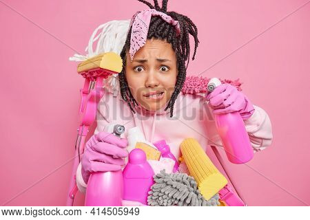 Isolated Shot Of Puzzled Dark Skinned Young Woman Bites Lips Poses With Cleaning Supplies Busy Doing