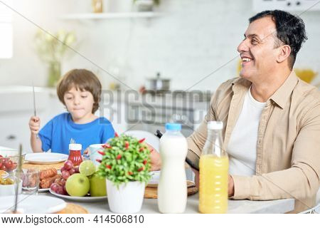 Cheerful Middle Aged Hispanic Man Smiling, While Having Breakfast With His Family, Sitting At The Ki
