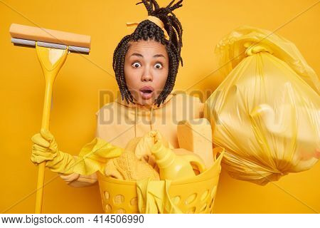 Shocked Surprised Ethnic Housemaid Wears Rubber Gloves For Hand Protection Holds Mop Trash Bag Basin