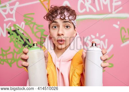 Photo Of Surprised Curly Haired Handsome Hipster Guy Uses Aerosol Spray For Drawing Graffiti Marks P