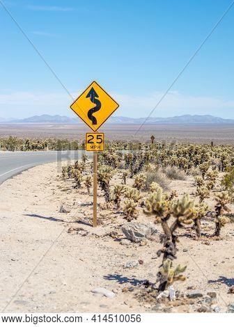 Yellow Traffic Sign, Winding Road In Mojave Desert, Joshua Tree National Park, California, Usa