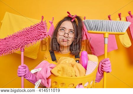 Regular Clean Up. Upset Tired Asian Woman Wears Latex Gloves Spectacles Holds Mop And Broom Being Si