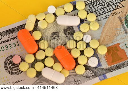 Hundred Dollar Bill Covered With Colorful Medical Pills. Money, Healthcare And Drug Trafficking Conc