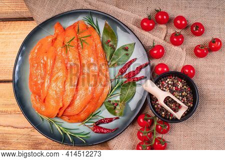 Chicken Fillet Thinly Sliced, Sottilissime In Red Marinade On A Plate With Vegetables On A Wooden Ta