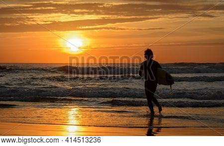Surfing Sunset. Silhouette Of Male Surfer Carrying Boards Along The Sand Of A Beach