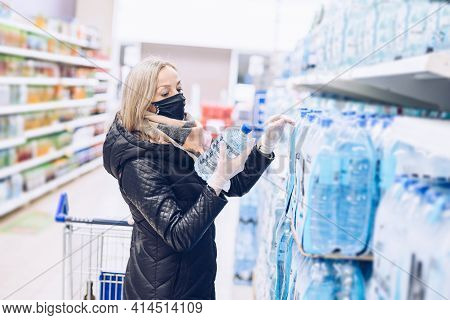 Woman Wearing Protective Mask Buys Water Bottles At Grocery Supermarket.