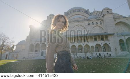 Beautiful Woman Poses At Mosque. Action. Happy Woman Twirls And Poses On Background Of Historic Temp