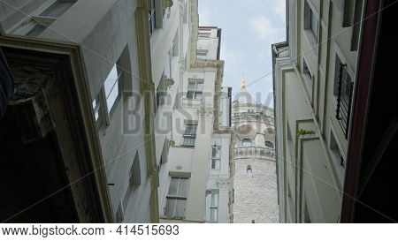 Galata Tower With Residential Buildings. Action. View From Below Of Medieval Tower In Center Of Old