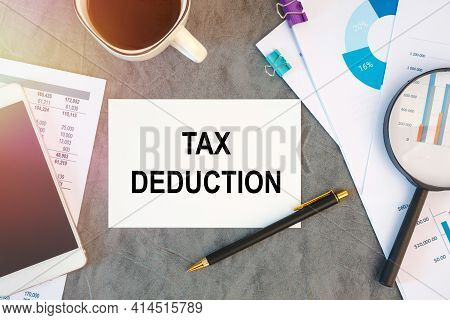 Tax Deduction Is Written In A Document On The Office Desk With Office Accessories, Keyboard And Diag