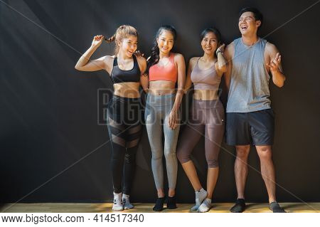 Asian Men And Women Groups Are Leaning Against The Black Wall While Waiting To Get Into The Fitness