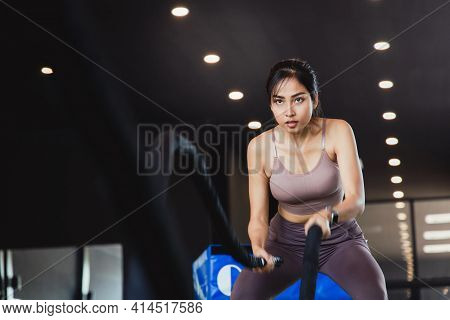 Strong Athlete Exercising With Battle Ropes At The Fitness Gym.  Women Good Shape Doing Battle Rope